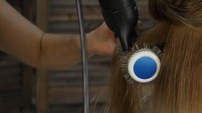 Mooie vrouw in schoonheidssalon De professionele Haaropmaker gebruikte een hairdryer Langzame Motie stock videobeelden