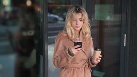 Mooie vrouw status buiten en het gebruiken van smartphone stock video