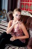 Mooie vrouw in studio, luxestijl Op bank Stock Foto's