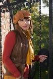Mooie vrouw vóór de gesloten gesmede poort. Stock Afbeelding