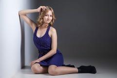 Mooie vrouw in violette kleding op grijs Royalty-vrije Stock Afbeeldingen