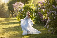Mooie vrouw in vliegende luchtige blauwe kleding in bloeiende lilac tuin royalty-vrije stock fotografie