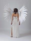 Mooie vrouw in witte kleding met engelenvleugels stock afbeeldingen