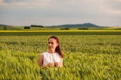 Mooie vrouw in witte kleding op groen tarwegebied Stock Foto's