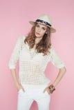 Mooie vrouw in witte kleren die op roze achtergrond in hoed stellen Stock Fotografie