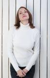 Mooie vrouw in witte poloneck bij de planking muur royalty-vrije stock fotografie