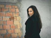 Mooie vrouw in zwarte dichtbij brickwall Het schot van de manier royalty-vrije stock afbeeldingen