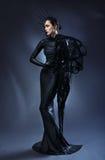 Mooie vrouw in zwarte Gotische kleding Het gezicht die een masker dragen Royalty-vrije Stock Foto