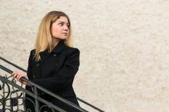 Mooie Vrouw in zwarte laag op oude treden van kasteel op muurachtergrond stock afbeeldingen