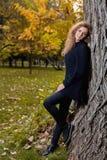 Mooie vrouw in zwarte sweater, die in de herfstpark stellen Royalty-vrije Stock Foto's