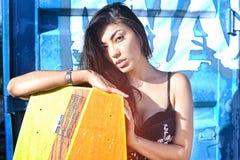 Mooie vrouw in zwarte witte kleding, lang haar die zich met wakeboad op het bacground blauwe ijzer bevinden, graffiti Royalty-vrije Stock Foto
