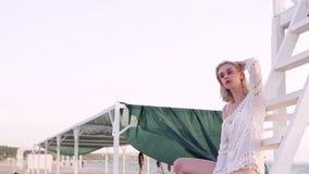 Mooie vrouw in zwempak het stellen op strand stock footage