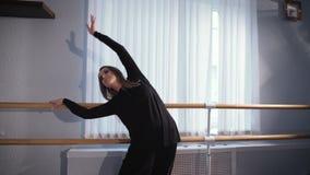 Mooie vrouwelijke balletdanser in zijde zwart kostuum die zich dichtbij balletstaaf bevinden in klaslokaal en schuine standen van stock video