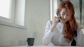 Mooie vrouwelijke beambte met rood haar en in wit overhemd die op telefoon stiitng bij de lijst spreken Portret stock videobeelden