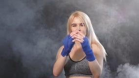 Mooie vrouwelijke bokser in blauwe handwraps worden die die voor grote strijd met rokerige achtergrond voorbereidingen wordt getr stock footage