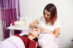 Mooie vrouwelijke cosmetologist die gezichtsbehandeling geven aan een donkerbruine cliënt in een schoonheidssalon royalty-vrije stock foto's