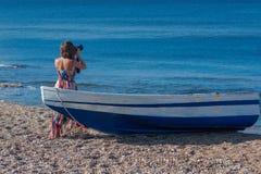 Mooie vrouwelijke fotograaf in de kleding met professionele camera dichtbij boot op het zand royalty-vrije stock fotografie