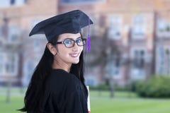 Mooie vrouwelijke gediplomeerde op campus royalty-vrije stock foto