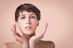 Mooie vrouwelijke gezichts dichte omhooggaand portret van jong model bij studio op pastelkleur stock afbeeldingen