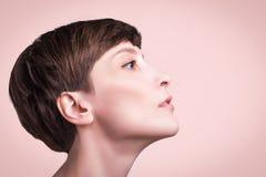 Mooie vrouwelijke gezichts dichte omhooggaand portret van jong model bij studio op pastelkleur stock foto