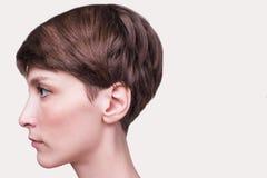 Mooie vrouwelijke gezichts dichte omhooggaand portret van jong model bij studio op wit stock foto's