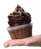 Mooie vrouwelijke hand die smakelijke smakelijke chocoladecupca houden royalty-vrije stock foto