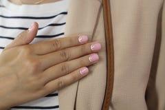 Mooie vrouwelijke hand met manicure Gevoelig roze nagellak met witte crescentsand en goed geconditioneerde vingers stock foto's