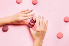 Mooie vrouwelijke handen met in manicure die roze makaroncake houden royalty-vrije stock foto's