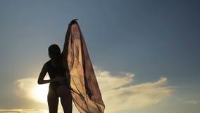 Mooie vrouwelijke het dansen en het houden transparante sjaal op het strand in langzame motie stock video