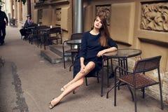 Mooie vrouwelijke modelzitting bij straatkoffie Stock Afbeeldingen