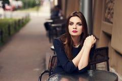 Mooie vrouwelijke modelzitting bij straatkoffie Stock Afbeelding