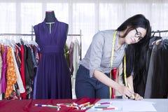 Mooie vrouwelijke ontwerper die nieuwe kleding trekken royalty-vrije stock afbeelding