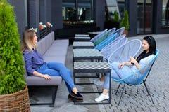 Mooie vrouwelijke personen die bij straatkoffie buiten zitten Royalty-vrije Stock Fotografie
