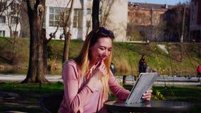 Mooie vrouwelijke persoon die met vrienden door tablet in park babbelen stock video
