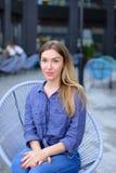 Mooie vrouwelijke persoonszitting bij koffie die buiten en blauw overhemd dragen Stock Foto