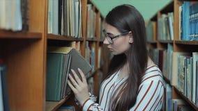 Mooie vrouwelijke student die een boek in de bibliotheek zoeken stock video