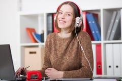 Mooie vrouwelijke student die met hoofdtelefoons aan muziek en het leren luisteren kijkend camera Royalty-vrije Stock Afbeeldingen