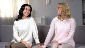 Mooie vrouwelijke vrienden handen en glimlachen houden die, verzoenend na ruzie stock foto's