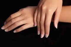 Mooie vrouwelijke wapens met ideale Franse manicure op zwarte achtergrond Zorg over vrouwelijke handen, gezonde zachte huid Kuuro Stock Afbeeldingen
