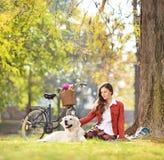 Mooie vrouwelijke zitting op een groen gras met haar hond in een park Stock Afbeelding