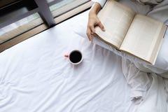 Mooie vrouwelijke zitting op het bed en lezing een boek Royalty-vrije Stock Afbeelding
