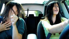 Mooie vrouwen in auto die terwijl het gaan in vakantie dansen stock videobeelden
