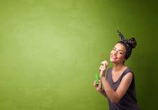 Mooie vrouwen blazende zeepbel op copyspaceachtergrond Stock Afbeelding