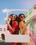 Mooie vrouwen die een leeg fotokader houden royalty-vrije stock afbeelding