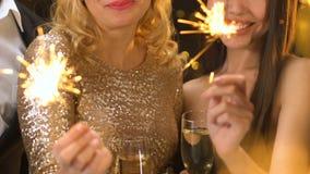 Mooie vrouwen die glazen met alcohol en van Bengalen lichten houden die nieuw jaar vieren stock footage