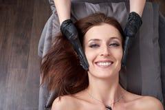 Mooie vrouwen die kosmetische procedure aangaande een gezicht ontvangen bij een cosmetologist in schoonheidssalon stock foto