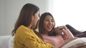 Mooie vrouwen die op een bank met afstandsbediening en het letten op video en film op televisie thuis liggen stock video