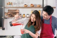 Mooie vrouwen gietende aardbei smoothie in een glas stock afbeelding