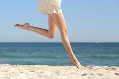 Mooie vrouwen lange benen die op het strand springen Stock Foto
