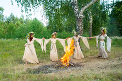 Mooie vrouwen met bloemkroon dichtbij vuur Stock Fotografie